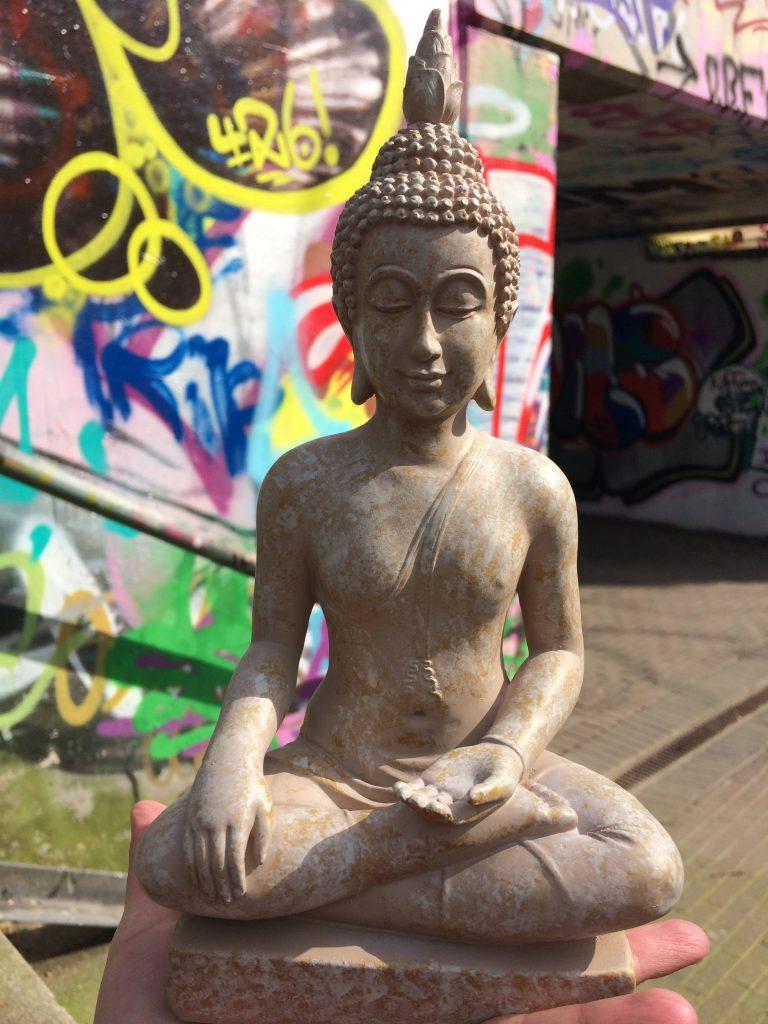 Beiger Buddha in Gladbeck vor Graffitiwand im Beitrag zu Vision Ziele Warum Psyche