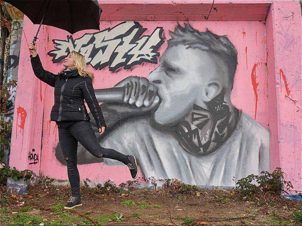Monika mit Schirm vor rosa Wand mit Rapper im Nordsternpark fackelnichtlang.de